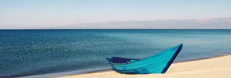 Small blue boat on the beach of a lake